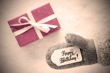 Label With English Calligraphy Happy Birthday. Gray Glove With Pink Gift And Snow Background And Snowflakes