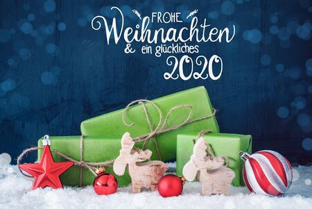 German Calligraphy Frohe Weihnachten Und Ein Glueckliches 2020 Means Merry Christmas And A Happy 2020. Green Christmas Present With Decoration Like Red Ball And Reindeer And Bokeh Effect