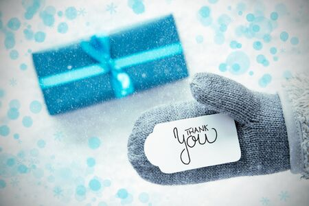 Label With English Calligraphy Thank You. Gray Glove With Turquoise Gift And Snow Background And Snowflakes