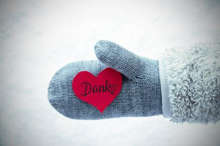 Red Heart With German Calligraphy Danke Means Thank You. Human Hand In A Glove With Fleece And Snow.