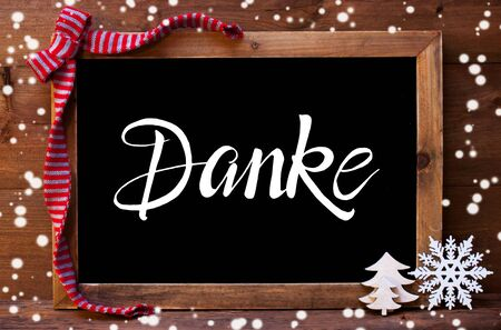 Chalkboard With German Calligraphy Danke Means Thank You. Christmas Decoration Like Tree And Bow. Wooden Background And Snowflakes Stock Photo