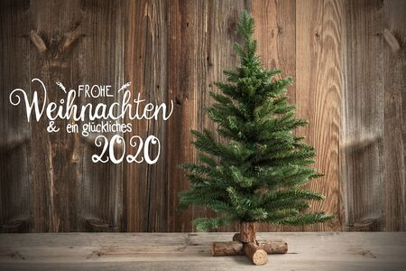 German Calligraphy Frohe Weihnachten Und Ein Glueckliches 2020 Means Merry Christmas And Happy New Year 2020. Christmas Tree Infront Of Brown Rustic Wooden Background