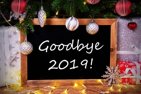 Blackboard With English Text Goodbye 2019. Christmas Tree With Ball, Gifts And Fairy Lights