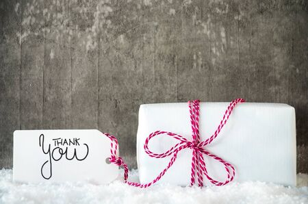 Label With English Calligraphy Thank You. White Christmas Present On Grungy Cement Background With Snow. Stock fotó