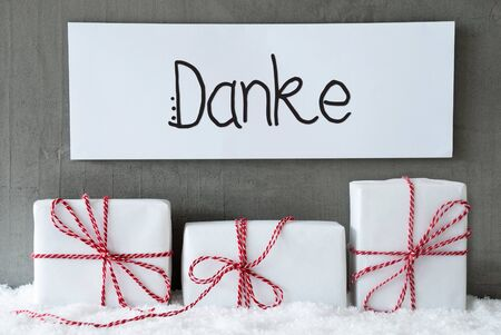 Sign With German Calligraphy Danke Means Thank You. Three White Gifts With Red Ribbon On Snow And Cement Background