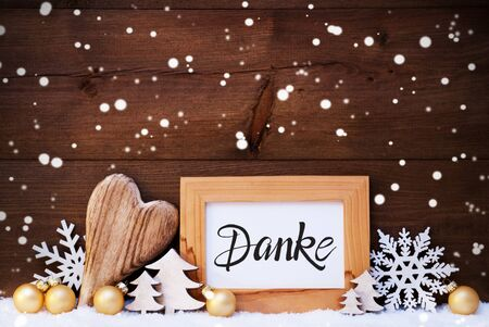 German Calligraphy Danke Means Thank You. Golden Christmas Ornament Like Ball, Heart And Tree. Wooden Background With Snow And Snowflakes