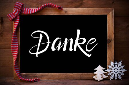 Chalkboard With German Calligraphy Danke Means Thank You. Christmas Decoration Like Tree, Snowflake And Bow. Wooden Background Stock Photo