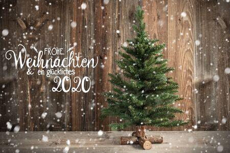 Duitse kalligrafie Frohe Weihnachten Und Ein Glueckliches 2020 betekent prettige kerstdagen en gelukkig nieuwjaar 2020. Kerstboom voor bruine rustieke houten achtergrond met sneeuw Stockfoto