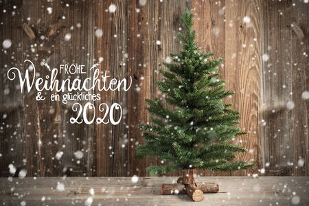 Niemiecka kaligrafia Frohe Weihnachten Und Ein Glueckliches 2020 oznacza Wesołych Świąt i Szczęśliwego Nowego Roku 2020. Choinka Infront Brązowe Rustykalne Drewniane Tło Ze Śniegiem Zdjęcie Seryjne
