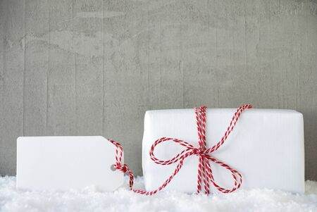 Label With Copy Space. One White Gift With Red Bow. Gray Concrete Background With Snow