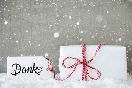 Label With German Calligraphy Danke Means Thank You. One White Gift With Red Bow. Gray Concrete Background With Snow And Snowflakes