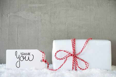 Label With Egnlish Calligraphy Thank You. One White Gift With Red Bow. Gray Concrete Background With Snow