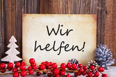Paper With German Text Wir Helfen Means We Help. Christmas Decoration And Wooden Background