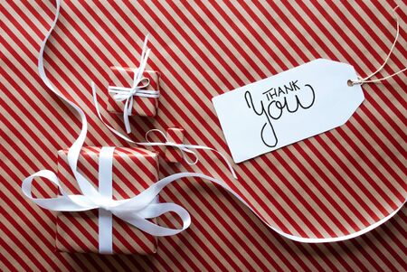 Label With English Text Thank You. Gifts And Presents On Red And White Wrapping Paper Stock Photo