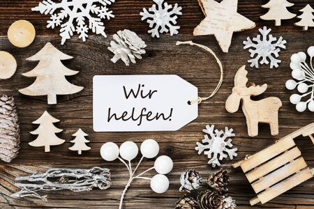 One White Label With German Text Wir Helfen Means We Help. Frame Of Christmas Decoration Like Tree, Sled, Star And Fir Cone. Wooden Background With Snowflakes