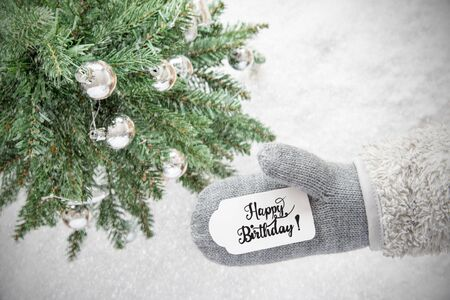 Glove With Label With English Calligraphy Happy Birthday. Christmas Tree With Silver Ball Ornament, Snow And Snowflakes