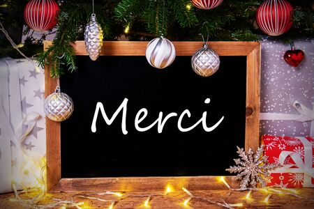 Blackboard With French Text Merci Means Thank You. Christmas Tree With Ball, Gifts And Fairy Lights Reklamní fotografie