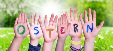 Children Hands Building Colorful German Word Ostern Means Easter. Green Grass Meadow As Background
