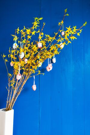 Easter Branch With Yellow Blossoms And Easter Eggs. White Ceramic Vase, Spring Decoration With Blue Wooden Background Imagens