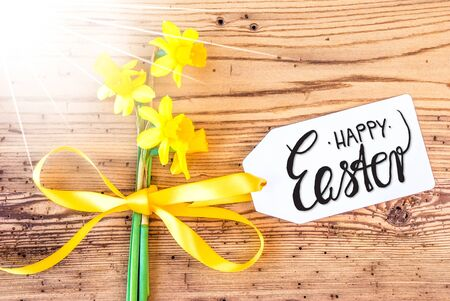 Label With English Calligraphy Happy Easter. Sunny Yellow Spring Narcissus Flower On Rustic Wooden Background. Imagens