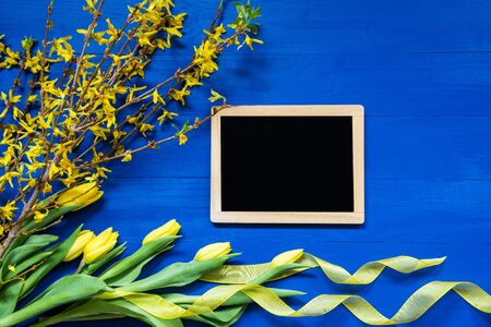 Chalkboard With Copy Space. Spring And Easter Decoration. Yellow Tulip Flowers, Branch And Ribbon. Blue Wooden Background