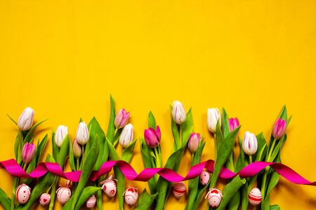 Decoration Of Colorful Tulip Spring Flowers With Easter Eggs. Yellow And Pink Blossoms With Pink Ribbon. Yellow Wooden Background