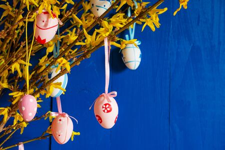 Easter Branch With Yellow Blossoms And Easter Eggs. Card With Spring Decoration. Blue Wooden Background