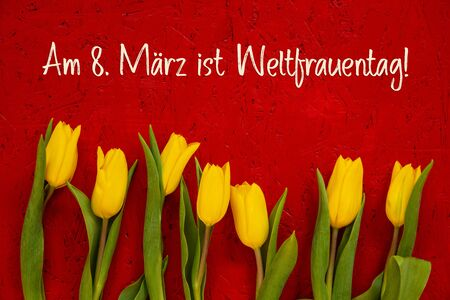 Red Wooden Background With German Text Am 8. März Ist Weltfrauentag Means International Womens Day. Yellow Tulip Flowers In Spring Season Stock fotó