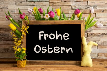 Blackboard With German Text Frohe Ostern Means Happy Easter. Colorful Tulip Spring Flower Decor. Brick Wall Background