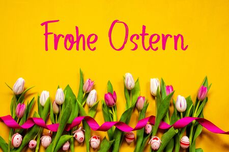 German Text Frohe Ostern Means Happy Easter. White And Pink Tulip Spring Flowers With Ribbon And Easter Egg Decoration. Yellow Wooden Background Imagens