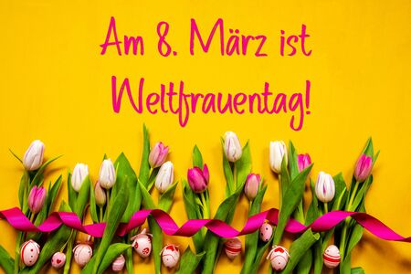 German Text Weltfrauentag Means International Womens Day. White And Pink Tulip Spring Flowers With Ribbon And Easter Egg Decoration. Yellow Wooden Background Imagens
