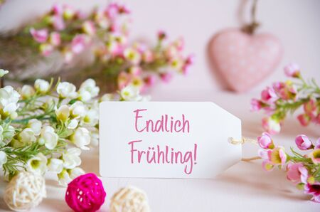 Label With German Text Endlich Fruehling Means Hello Spring. Rose And White Flowers With Heart Decoration.