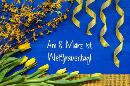 German Text Weltfrauentag Mean International Womens Day. Yellow Spring Flowers Like Tulip And Branches. Festive Decoration With Ribbon. Blue Wooden Background