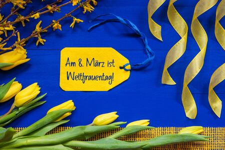 Label With German Text Weltfrauentag Mean International Womens Day. Yellow Spring Flowers Like Tulip And Branches. Festive Decoration With Ribbon. Blue Wooden Background Imagens