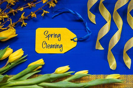 Label With English Text Spring Cleaning. Yellow Spring Flowers Like Tulip And Branches. Festive Decoration With Ribbon. Blue Wooden Background