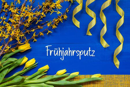 German Text Fruehjahrsputz Means Spring Cleaning. Yellow Spring Flowers Like Tulip And Branches. Festive Decoration With Ribbon. Blue Wooden Background Imagens