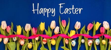 English Text Happy Easter. Banner Of White And Pink Tulip Spring Flowers With Ribbon And Easter Egg Decoration. Blue Wooden Background Imagens