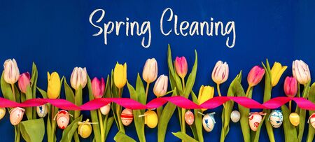 English Text Spring Cleaning. Banner Of White And Pink Tulip Spring Flowers With Ribbon And Easter Egg Decoration. Blue Wooden Background