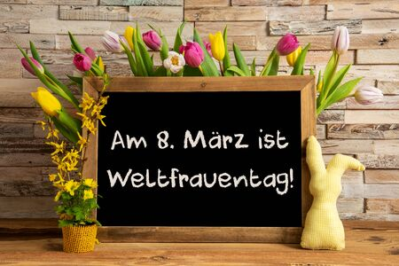 Blackboard With German Text Weltfrauentag Means International Womens Day. Colorful Tulip Spring Flower Decor. Brick Wall Background Imagens