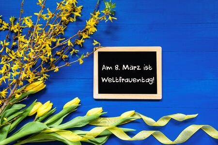 Blackboard With German Text Weltfrauentag Mean International Womens Day. Yellow Spring Flowers Like Tulip And Branches. Festive Decoration With Ribbon. Blue Wooden Background Imagens