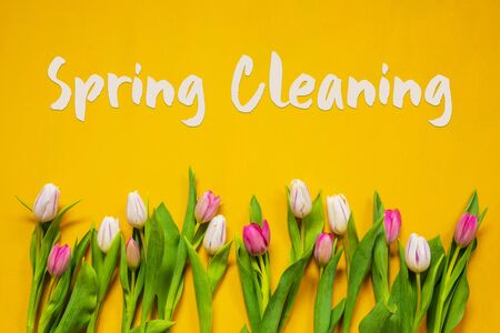 English Text Spring Cleaning. White And Pink Tulip Spring Flowers. Yellow Wooden Background
