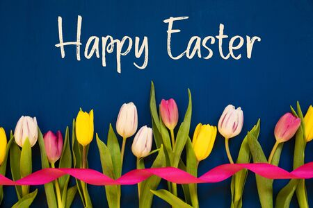 English Text Happy Easter. White And Pink Tulip Spring Flowers With Ribbon. Blue Wooden Background