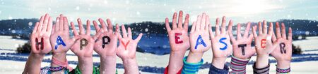 Children Hands Building Colorful Word Happy Easter. White Winter Landscape With Snow As Background