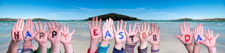 Children Hands Building Colorful Word Happy Easter Day. Ocean With Sandy Beach As Background Imagens