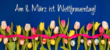 German Text Weltfrauentag Means International Womens Day. Banner Of White And Pink Tulip Spring Flowers With Ribbon And Easter Egg Decoration. Blue Wooden Background