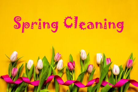 English Text Spring Cleaning. White And Pink Tulip Spring Flowers With Ribbon. Yellow Wooden Background