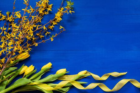Spring And Easter Decoration. Yellow Tulip Flowers And Branch. Blue Wooden Background With Copy Space