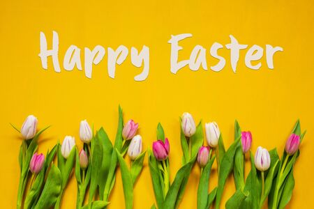 English Text Happy Easter. White And Pink Tulip Spring Flowers. Yellow Wooden Background