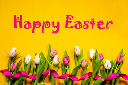 English Text Happy Easter. White And Pink Tulip Spring Flowers With Ribbon. Yellow Wooden Background