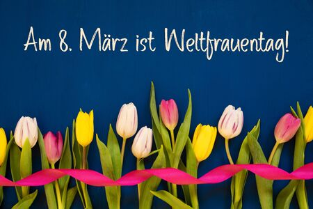 German Text Weltfrauentag Means International Womens Day. White And Pink Tulip Spring Flowers With Ribbon. Blue Wooden Background Imagens